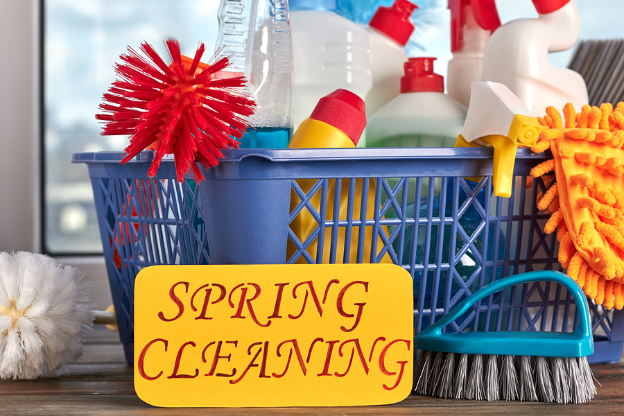 "Blue bucket of Cleaning supplies and brushes with yellow sign saying ""Spring Cleaning"" in the front."